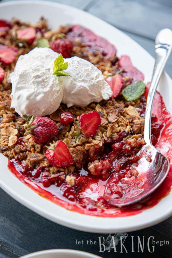 Strawberry rhubarb crisp with fresh cream in a white porcelain baking dish with silver spoon