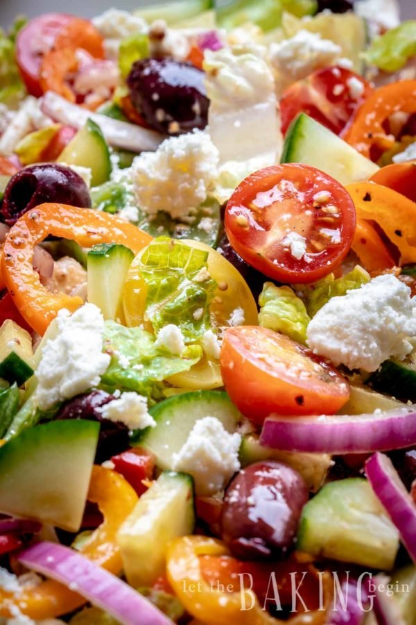 Healthy easy Greek salad close up of feta, lettuce, tomato and onion with Greek salad dressing