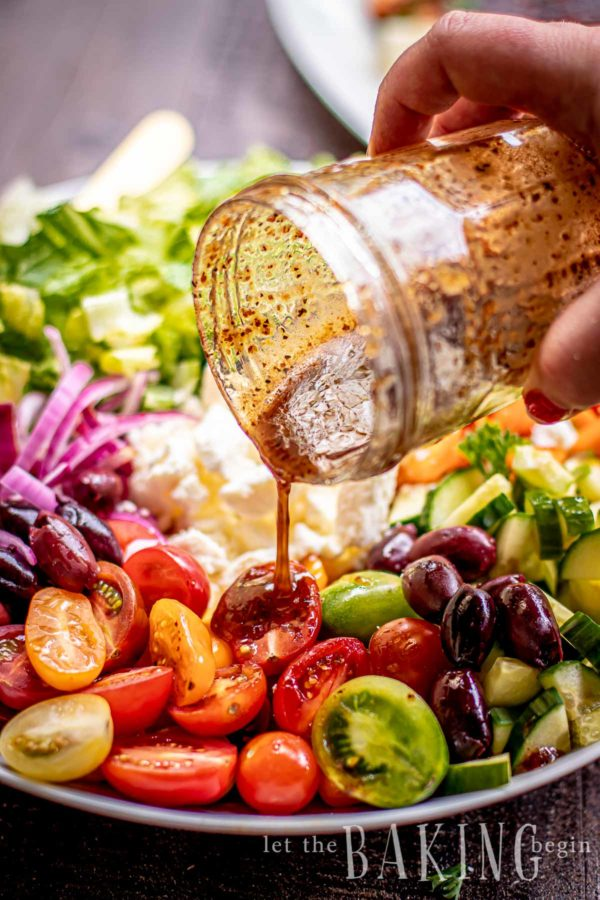 Homemade Greek salad dressing being poured out of a mason jar onto salad.