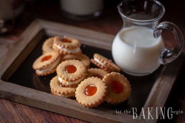 Linzer cookies piled on a tray with a jug of milk