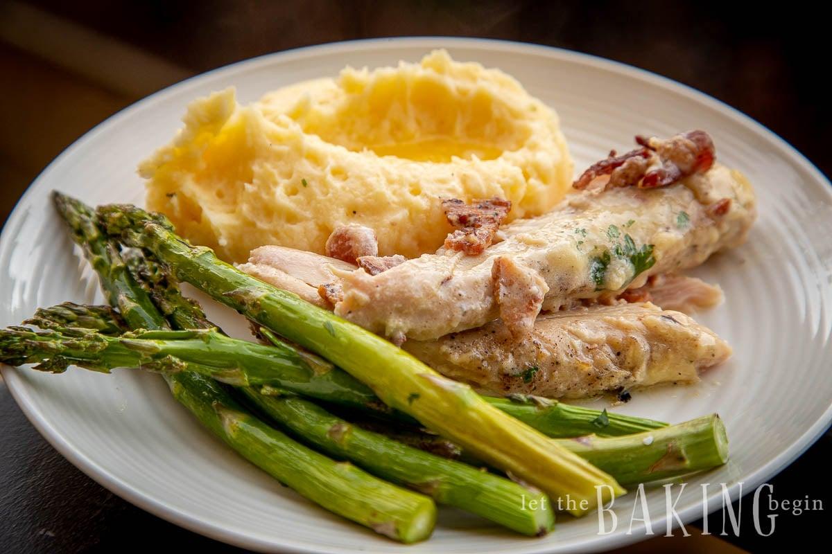 Plato con porciones de una receta de tocino de pollo, asparagu y puré de papas esponjoso.