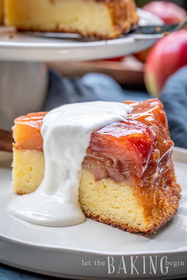 A slice of an upside down apple cake with a sour cream topping.