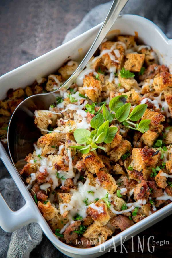 White serving dish filled with an easy stuffing recipe topped with fresh basil.
