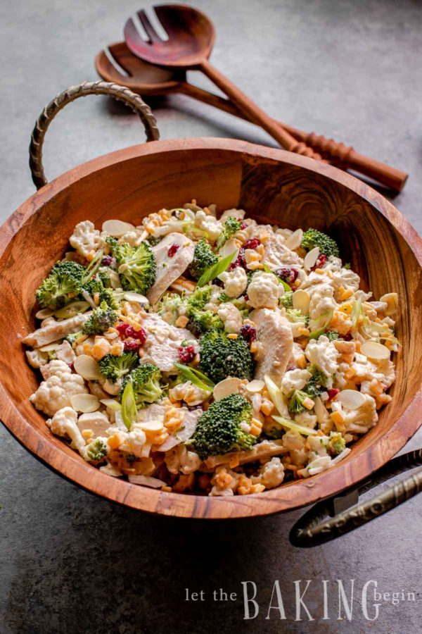 Broccoli crunch salad made in a bowl with utensils in background.