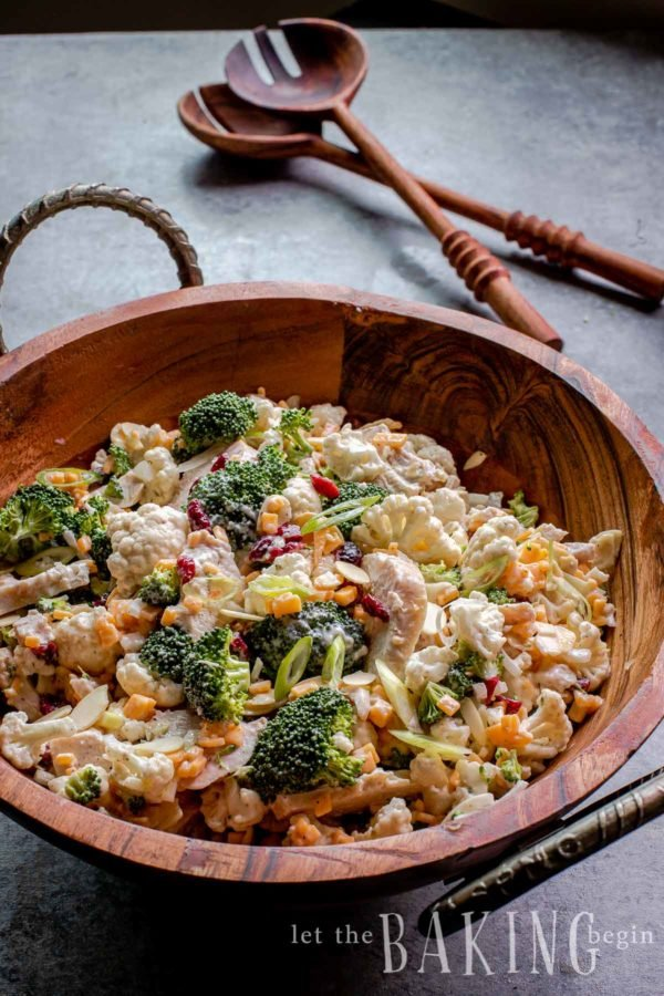 Broccoli cauliflower salad tossed together in a wooden bowl with utensils in background.