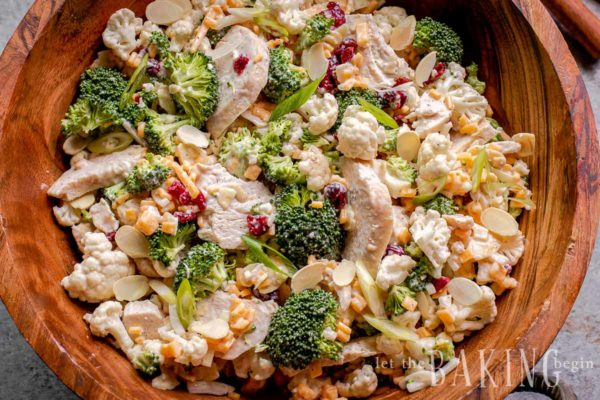 Close up of cauliflower broccoli salad in a wooden bowl.