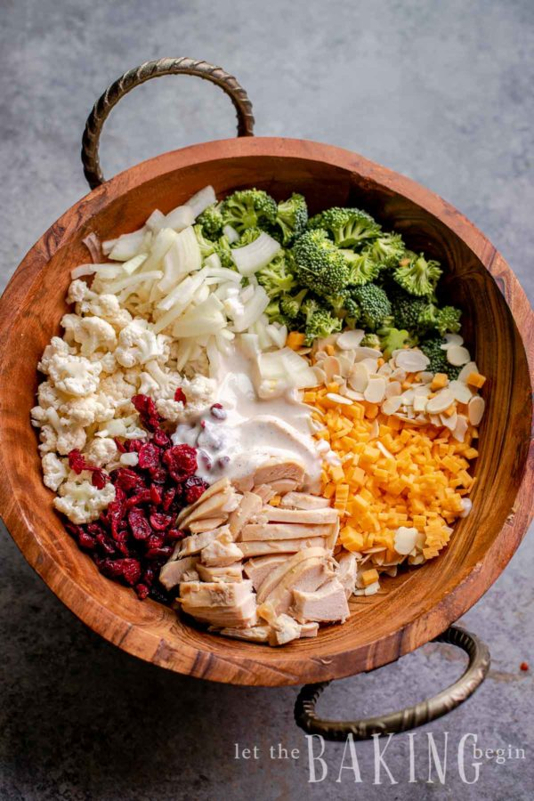Cauliflower broccoli salad in a wooden bowl before it's tossed together.