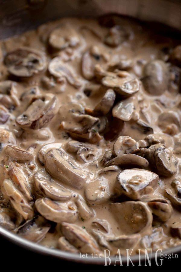Close up of mushroom sauce with thickly sliced mushrooms in it.