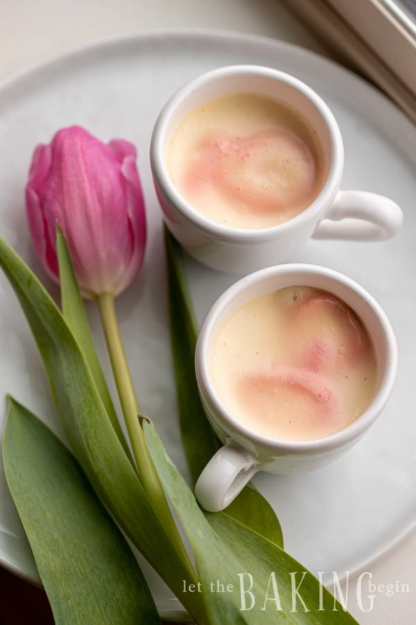 A no bake dessert (panna cotta) on a white tray with a pink tulip next to it.