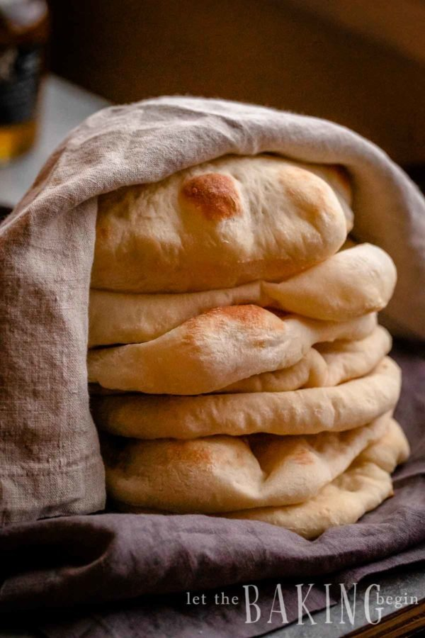 Stack of pita bread with a towel on top.