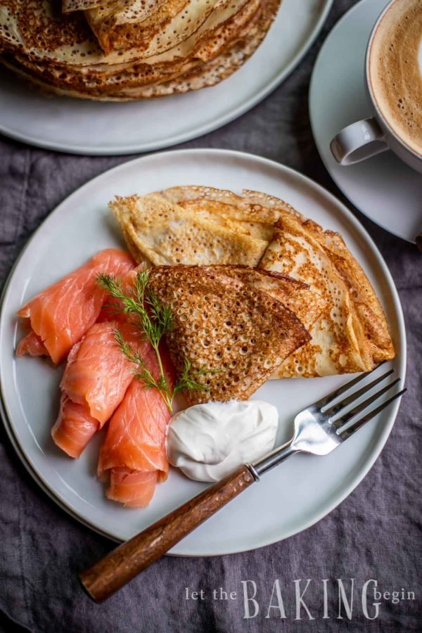Lacey, thick blini crepes folded with salmon and sour cream on a plate.