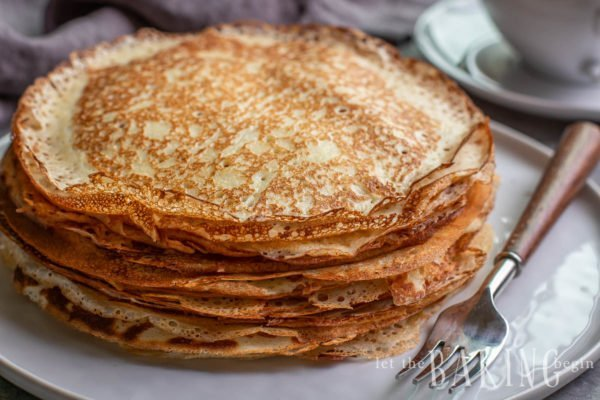 Close up of a stack of Russian crepes on a plate with a fork.