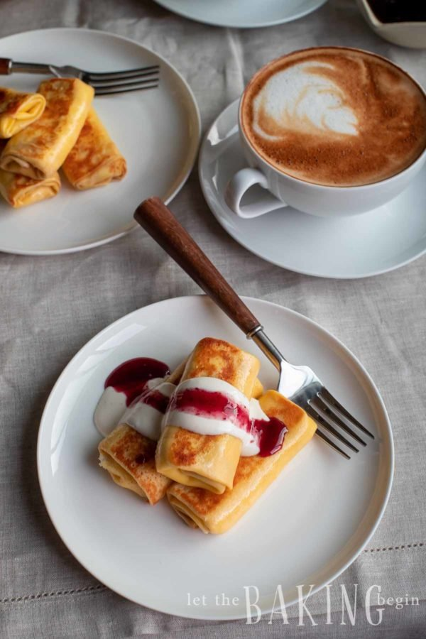 Stack of blintz on a plate. Each is stuffed with a cheese filling and has a ribbon of jam and cream on the top.