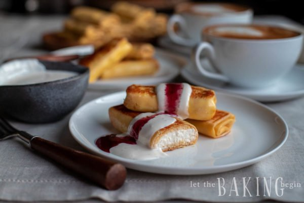 Prepared cheese blintz recipe on a plate. Each one has a creamy cheese filling and is topped with a ribbon of sour cream and jam.