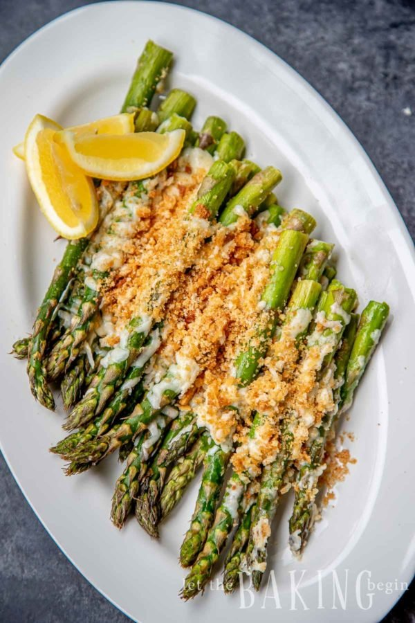 Top shot of the Baked Asparagus with Cheese on a white plate, with lemon wedges.