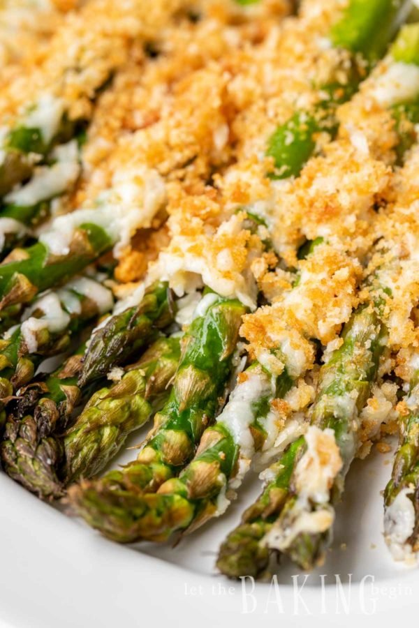 Close up of baked asparagus with melted cheese and Ritz Cracker crumbs on top.