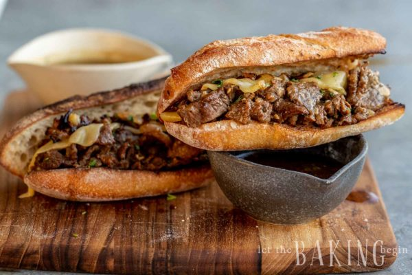 Two French dip sandwich halves on a wooden cutting board with two dipping bowls.