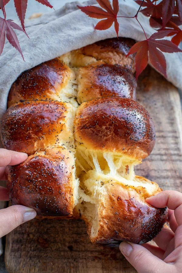 Brioche Bread being pulled apart by hands.