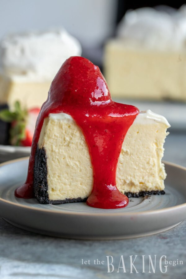 a slice of Instant pot cheesecake with an oreo crust topped with strawberry purée