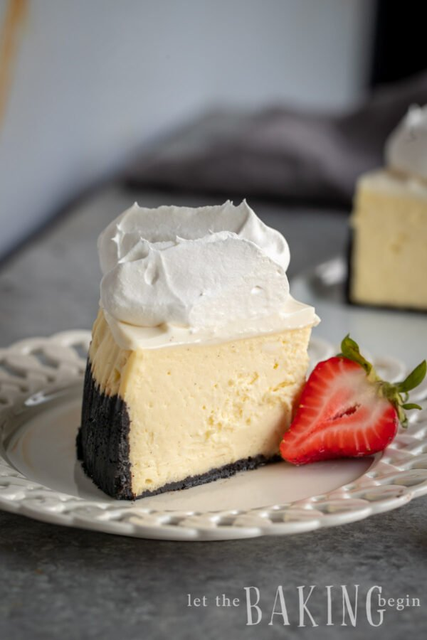 Slice from a New York style cheesecake recipe with strawberry next to it