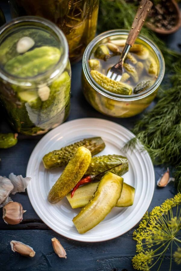 Homemade pickles next to a jar of a made pickle brine recipe.