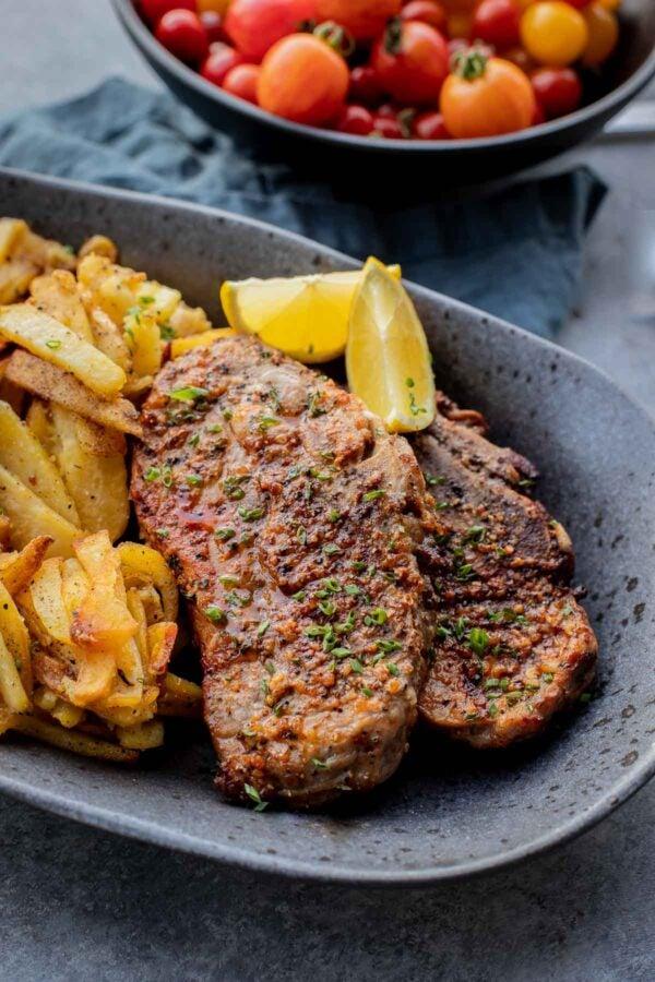 air fryer pork chops on a plate with lemon wedges