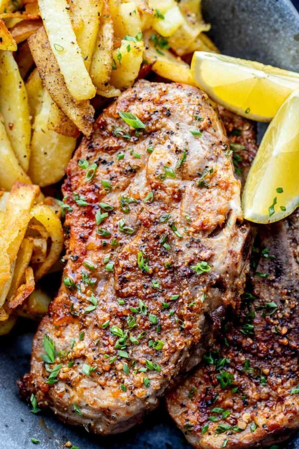 air fryer cook chops recipe with french fries and lemon wedges