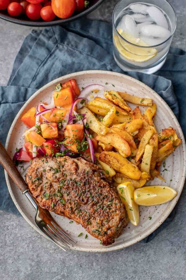 air fryer pork chops on a plate with chopped tomatoes and fries