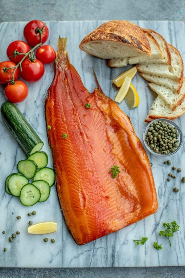 salmon with cucumber, tomatoes, and sliced baguette on a marble background