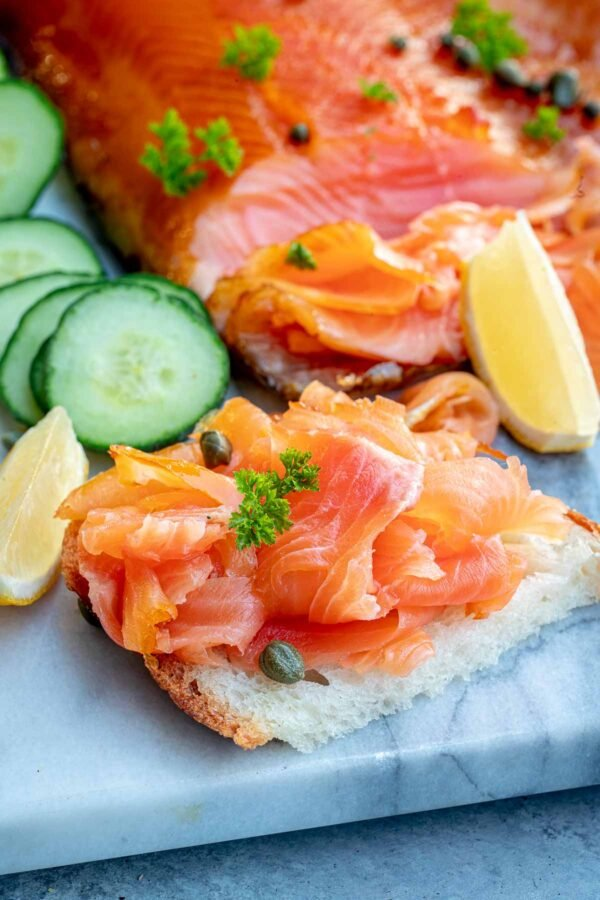 Close up of smoked salmon recipe piled onto bread with cucumbers