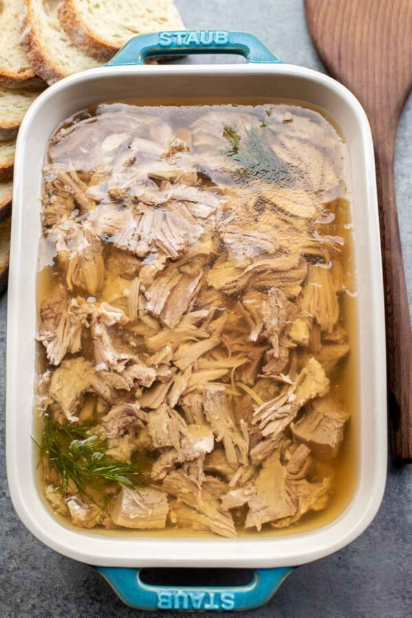Baking dish full of kholodets of meat aspic surrounded by bread and a spoon.