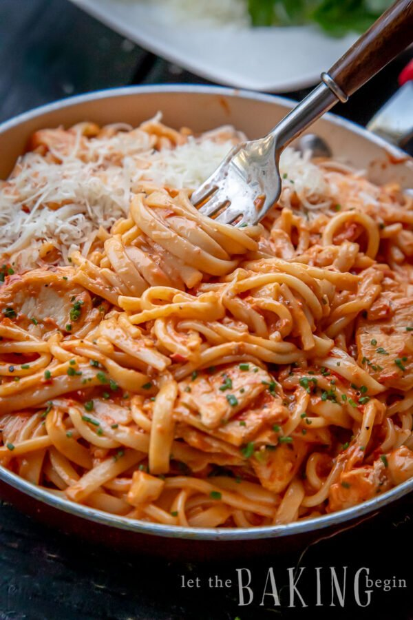 Fork twirled in pasta coated in a tomato cream sauce