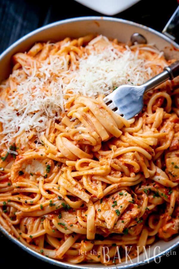 A fork twirling in a pan of tomato pasta