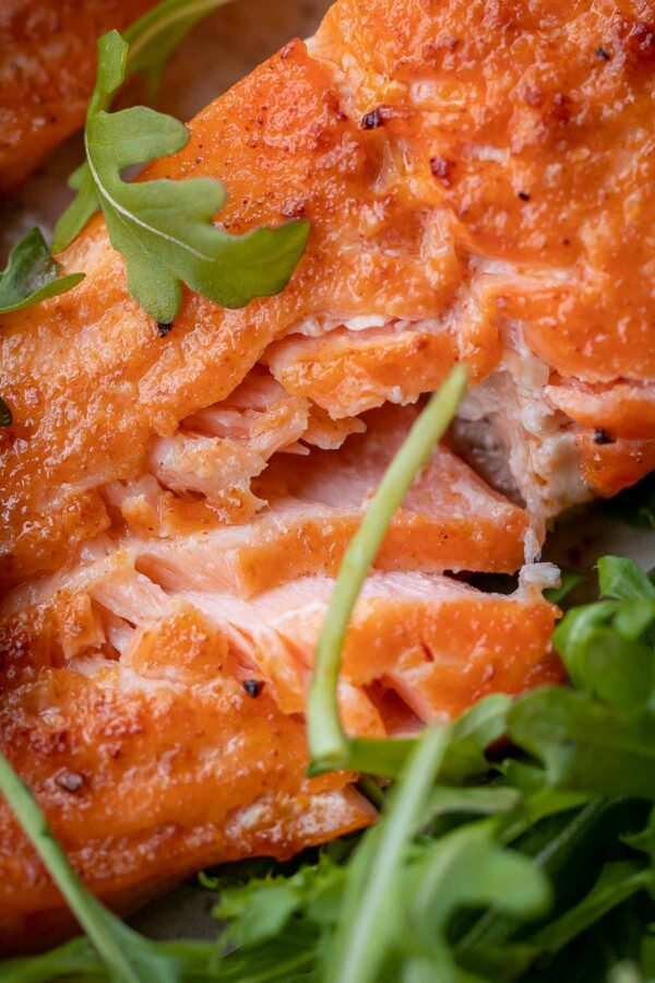 Air Fried Salmon fillet on a bed of arugula with flakes of salmon exposing the juicy center.