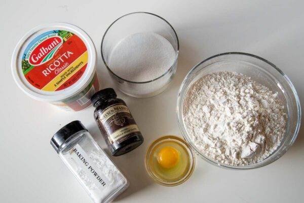 ingredients for mini donuts including ricotta cheese, flour, egg, sugar