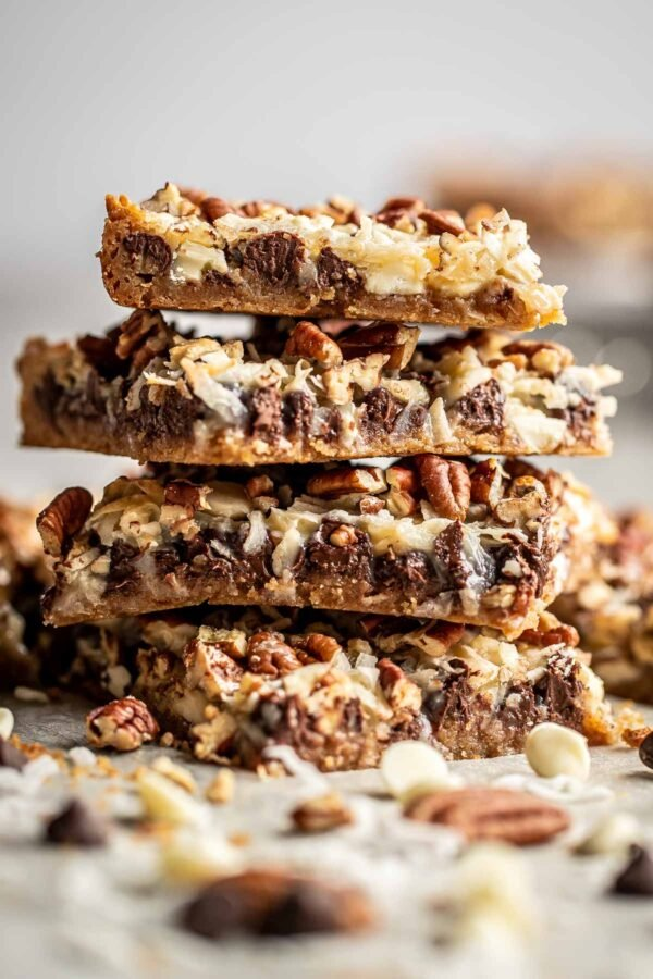 Stack of magic cookie bars with coconut and nuts sprinkled in the foreground