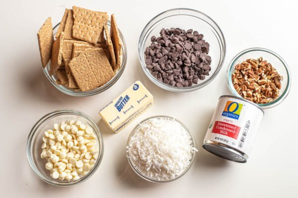Ingredients for 7 layer bars such as graham crackers, chocolate chips, butter, coconut and condensed milk