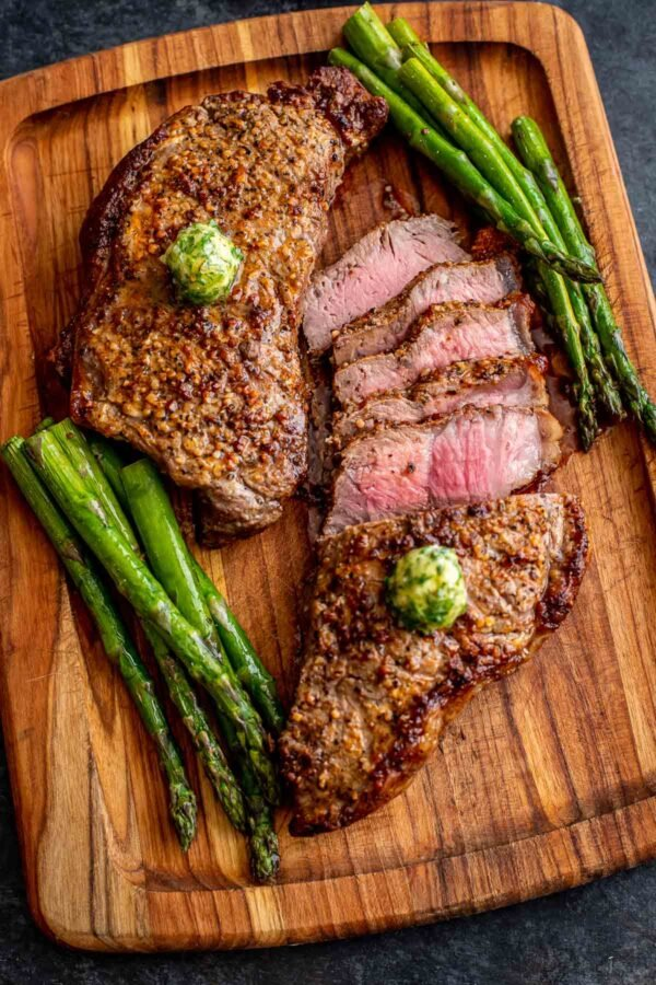 Steak in an air fryer that has been removed from the appliance and sliced on a wooden cutting board next to asparagus.