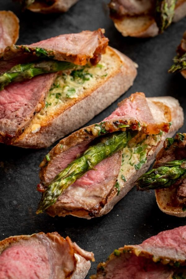 air fryer steak wrapped around asparagus on a slice of baguette with herb butter