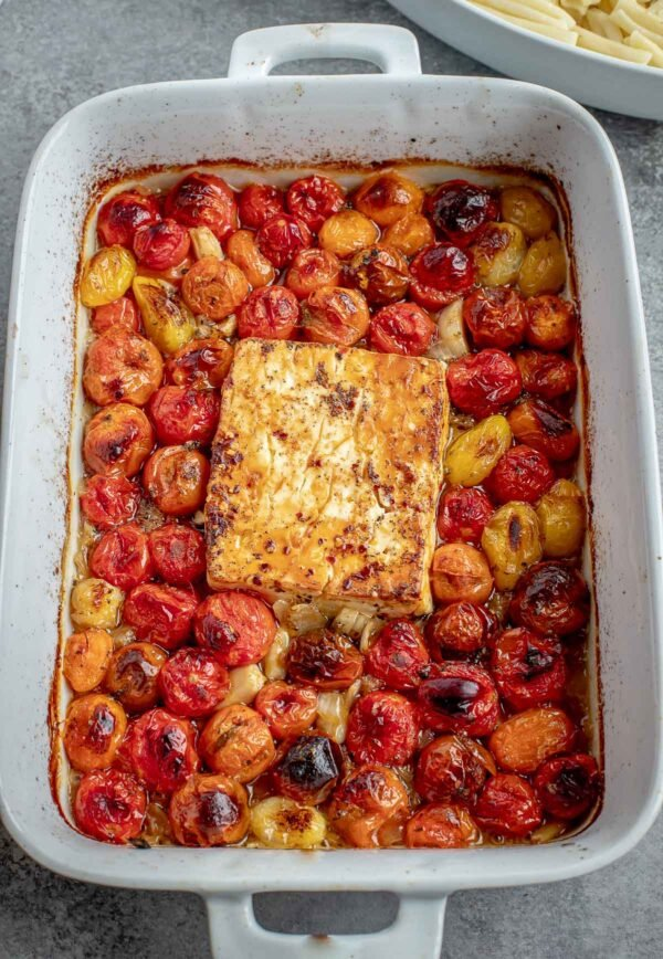 A baking dish with the roasted tomato pasta base cooking together with a block of feta cheese.