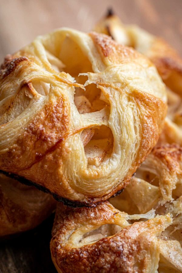 Apple turnover close up with flaky layers of blitz puff pastry exposed.