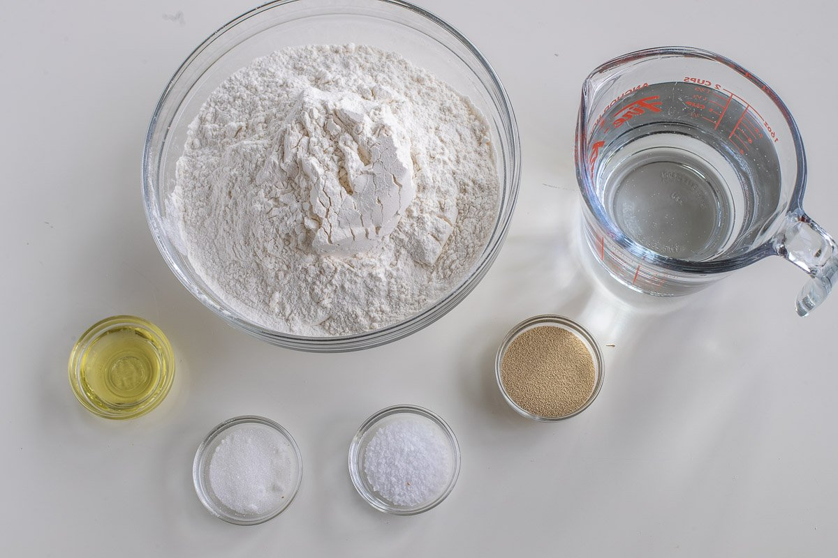 Ingredients for bread machine pizza dough in glass bowls, including flour, oil, and other seasonings.