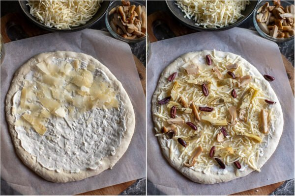 Bread machine pizza dough rolled out on wax paper with cheese and toppings being added on top.