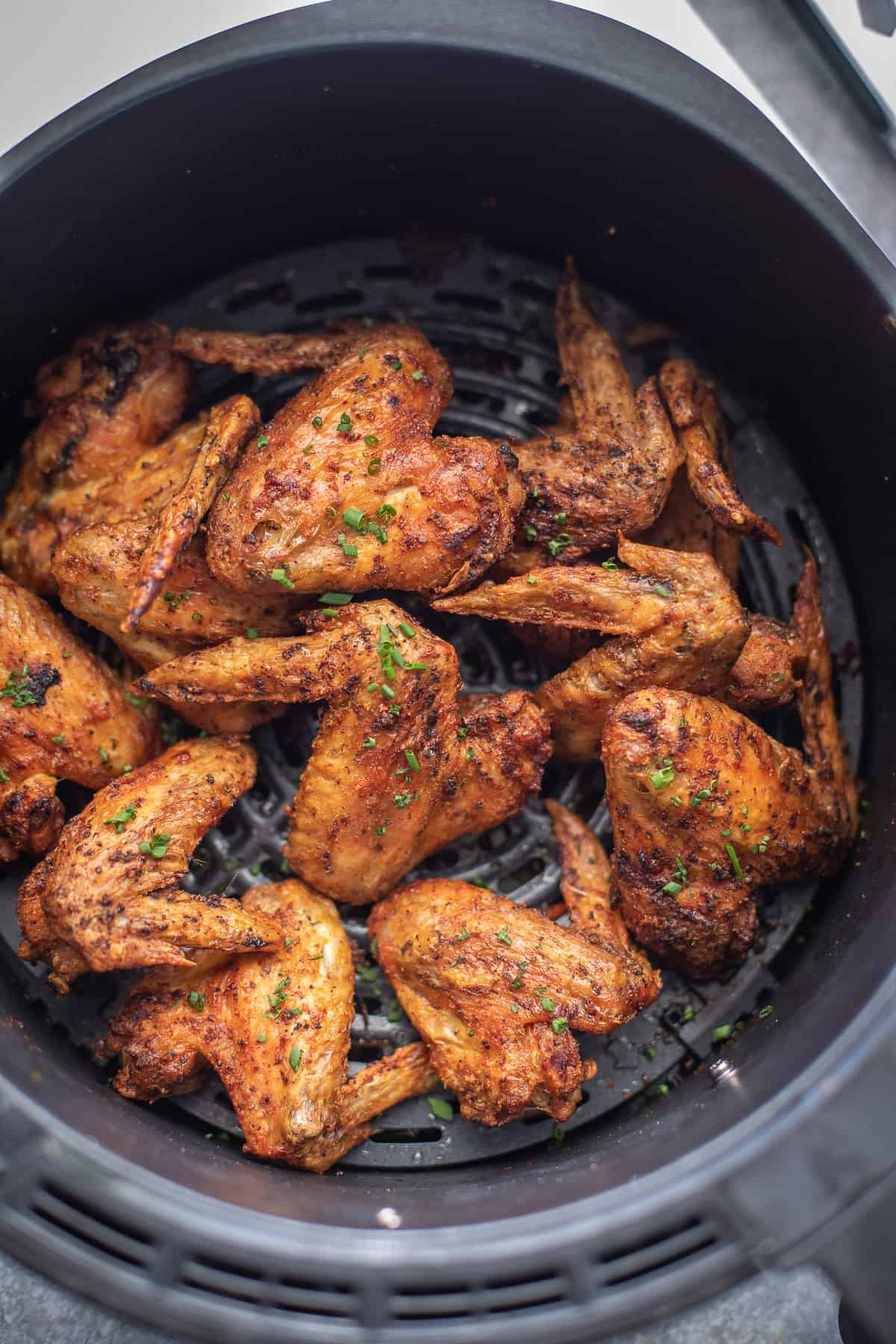 Chicken wings in the air fryer, overhead view.