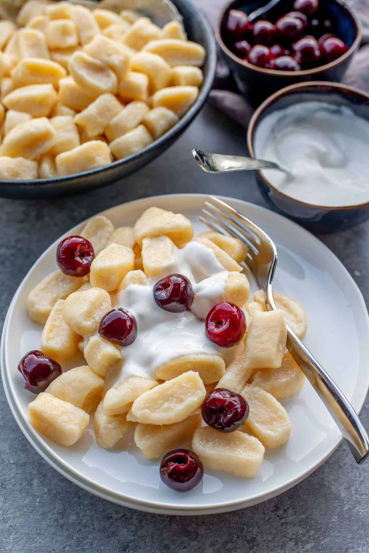 Plates with lazy pierogi, drizzled with sweetened sour cream and cherries.