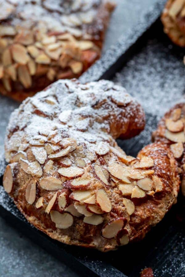 Top view of a baked almond croissant sprinkled with powdered sugar on half of the croissant.